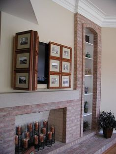TV above fireplace hidden behind bifold hinged photo frames