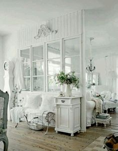 A whitewashed Coastal Cottage interior with vintage iron bench, clock