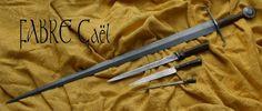 """Epée civile au milieu du XVème siècle.Un exemple d'épée feuilletée tel que l'on pouvait en trouver au milieu du XVème siècle. Ici, un modèle inspiré d'épées retrouvées dans la Dordogne. Cette dernière est accompagnée d'une dague feuilleté civile dite """"à couillette"""", et d'un set de cuisine feuilleté lui aussi (couteau et fusil). Cette épée possède une lame feuilletée d'environ 800 couches d'acier qui mesure 82cm de longueur, d'une largeur de 5 cm et de 6 mm d'épaisseur au talon."""