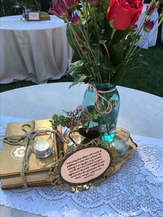 Centerpieces for Dream Catcher Grad: Clothbound vintage books, quotes by the valedictorian grad, brass and florals in tall masons.