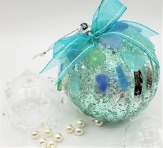 """Beach Christmas ornament.  This lovely wintergreen ball ornament totally says """"coastal""""!  It's a 4"""" acetate mercury glass ball in a fabulous spearmint or wintergreen color, accented with blingy glass """"ice"""".  We add our """"Ocean Mix"""" sea glass to amp up the coastal charm and the gorgeous color and a matching organza bow. Sweet, simple, and super beachy!  And LOVE that color!  Perfect for any coastal decor!  4"""" ball, about 4.25"""" diameter w the addition of the sea glass."""