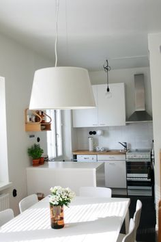 Love the over-sized light fixture above the table and all white keeping this clean and simple
