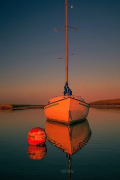Red Sunrise Reflections On Sailboat. Cape Cod seascape photography for sale by photographer Dapixara.