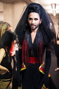 Conchita Wurst walked down the runway in a floor-length black gown embellished with gold and red, as well as matching black elbow-length gloves and veil. Her beard, as ever, was immaculate. #GothicBearedBride