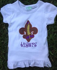 Smock Your Tot - Appliqued Fleur De Lis Purple and Gold T-Shirt or Onesie, $24.95 (http://www.smockyourtot.com/appliqued-fleur-de-lis-purple-and-gold-t-shirt-or-onesie/)
