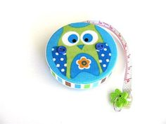 Blue owls cover both sides of this fabric covered, retractable pocket tape measure. Each has tints of lime green and orange.The front owl has a 2 button embellishment. A button charm is attached to the tapes pull tab and the entire tape is encircled with coordinating ribbon.     I carry a tape measure everywhere! You cant imagine how many times it came in handy and often has been borrowed in a store. Keep it in your purse for shopping and crafts on the go. It is small, only 2 (5cm) across…