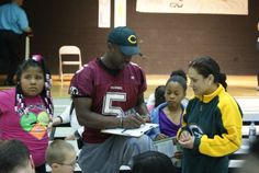 Veteran Racine Raiders defensive back Tracy Baskin signs autographs for students at Julian Thomas Elementary School as part of the Reading with the Raiders program.