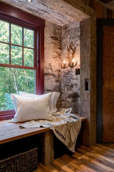 A thoughtful design makes the most of the limited space in this cozy mountain cabin. The former carriage house features a rustic style, with rough-hewn wood and exposed beams throughout. An open bedroom is concealed behind double black doors, which add nice contrast to all the wood in the house.