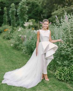 House of Ollichon loves...Real Brides Who Nailed the Bridal Jumpsuit Look. It's hard to say no to pants when they have the same wow factor as a ballgown skirt. This full, princess-worthy bottom was balanced out with a sleeveless, formal top. The entire ensemble, by Azzi and Osta, rivaled any fairytale dress. Bride in a Wedding Jumpsuit with a Train. #detachablebridalskirt #bridaloverskirt #overskirt