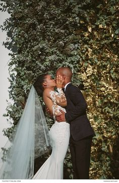 An African couple shared a kiss in front of a backdrop of foliage on their wedding day. | Photographer: Kristi Agier Photography | Wedding Dress Designer: Casey Jeanne | Florist: Leipzig Floral Design