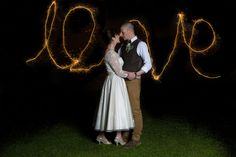 The bride & groom on their wedding day at Jimmy's Farm, Suffolk with LOVE written with a sparkler. www.headoverheelsphotography.co.uk