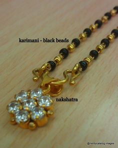 Gold and black bead necklace with a zircon nakshatra pendant