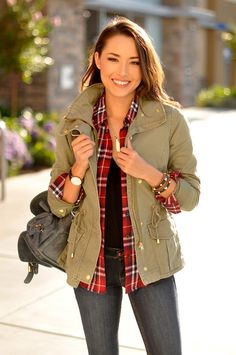 Green, olive and gold utility jacket with sweater and red plaid flannel shirt. Skinny jeans and black backpack.