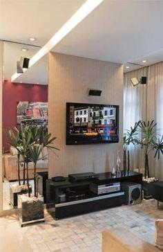 A sensação de amplitude vem dos espelhos verticais que emolduram a TV, fixada em um painel de gesso acartonado coberto de papel de parede. O rack é de laca preta brilhante. Abriga o receiver do home theater, o aparelho de blu-ray, o conversor de TV a cabo e o roteador.
