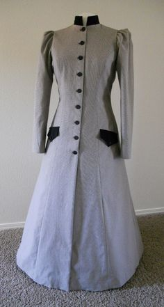 This coat is eminently suitable for a late victorian steampunk look or could be shortened for a more modern feel.    Made in a medium to heavy weight cotton fabric with a small black, cream & beige check pattern (which the camera didn't like very much) it has black velvet accents and black taffeta lining. It is fully lined, has two front pockets, black front button closures with a wide pleat at the center back waist that has enough fullness to accomodate a small bustle underneath if desired…