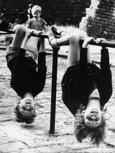 Two children have fun hanging upside down off a low rail in stockport, 1966 photo by Shirley Baker.