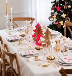 white table cloth, simple dinnerware, gold cutlery, pink accents