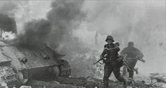 SS-Panzergrenadiers of 3. SS-Panzergrenadier-Division 'Totenkopf' pass behind a burning and destroyed T-34, make signs for the SS-Kriegsberichter to leave the area during battles raged around the Starówka (Old Town). Warsaw, Poland. 18 August 1944.