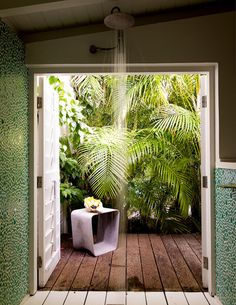 Oh, if only every bathroom opened onto its own tropical garden! When the area just outside of the powder room is this good, it almost doesn't matter what's indoors. Nevertheless, this space celebrates the power of verdant greenery with mosaic-style green tiles