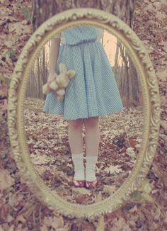 looking glass. I can't help but notice hos the blue dress and the looking glass are like Alice, but she is wearing red slippers like Dorothy...