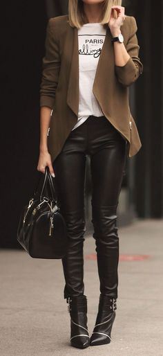 Den Look kaufen: https://lookastic.de/damenmode/wie-kombinieren/strickjacke-mit-offener-front-t-shirt-mit-rundhalsausschnitt-enge-hose-stiefeletten-satchel-tasche-uhr/6747 — Schwarze verzierte Leder Stiefeletten — Schwarze Satchel-Tasche aus Leder — Schwarze Enge Hose aus Leder — Braune Strickjacke mit offener Front — Weißes und schwarzes bedrucktes T-Shirt mit Rundhalsausschnitt — Schwarze Uhr