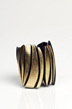 "MONIES Gold Foil Ebony Bracelet, $470.00 now (as of Jan. 2014) $376.00 (20% off), Gold foil on ebony bracelet with elastic fit. 3.5"" high, 11"" circumference. Made in Denmark"