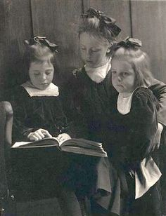 Three young girls reading a book, ca. 1900