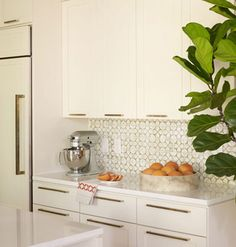 Gold hardware is mounted horizontally on cabinet doors for a sleeker look. Cabinet fronts cover the refrigerator and dishwasher, allowing th...