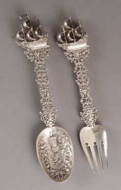"""2 Continental / Belgian silver serving pieces.  A Belgian silver serving fork and spoon. 1777. With ship motif and coat of arms on spoon. 11 1/4""""l x 2 1/3""""w. 9.300 toz."""