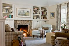 Stone fireplace with white cupboards and easy armchair http://www.in-form-design.com