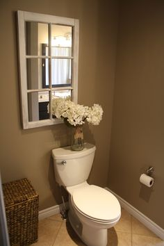 Country bathroom décor, hydrangeas in a jar, old window mirror.