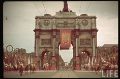 """Dressed in Ancient Germanic regalia, participants in the grand cultural display parade fourth through the arches of a monument as thousands of German citizens gaze at the spectacle. Hitler sought to integrate pagan beliefs into German society, believing it would invoke a strong warrior culture among the masses. Proposed was a """"Day of German Art"""". A way to reconnect the German people to their ancient pagan roots was a grand show of glorious displays of pagan symbology and tradition."""