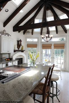 Vaulted Ceiling and fireplace in this fab kitchen. The lite grey granite With white and dark Wood.