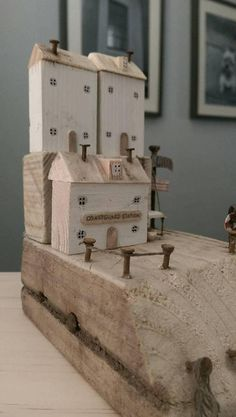 Made entirely from reclaimed wood, this original design shows the Coast guards station house with lean-to and boat, sitting below 2 white coastal cottages. Other features include a rope ladder, metal work, sailboat, Coast Guard sign, weathered rope, flagpole, attic roofs and metal