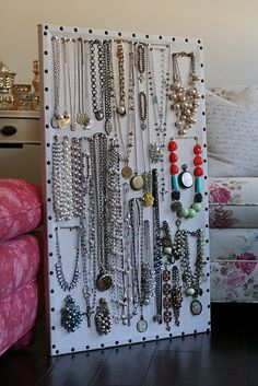 Jewelry Center.   Use a 24x36 cork/message board  covered it with linen or burlap, upholstery tacks, measure & nail them around the border.  Use nickel plated style push pins to hang jewelry.