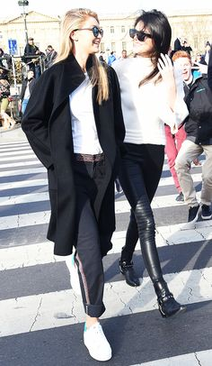 Gigi Hadid wears a white t-shirt, black coat, stitched trousers, and platform sneakers. Kendall Jenner wears a white top, leather pants, and black motorcycle boots