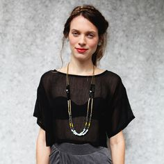 Layering necklace over flowing blouse tucked into high-waisted skirt
