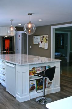 Beautiful White cabinet and carrara marble countertop is a major feature in this Rhode Island Kitchen. The white island with furniture legs seating for 5 and wine and mini fridge is a chef's dream. Modern and sleek is the design feature which was achieved by the implementation of Modern Clear glass globe pendants, Black and chrome bar stools,Blue glass mosaic backsplash, brushed nickel bar pulls and finally a weathered oak floor. #RhodeIslandKitchen #RhodeIslandContractor…