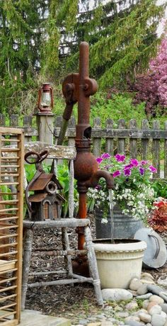Garden...rusty water pump blends well with the chipped old chair, birdhouse, and flowers.