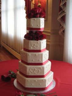 5 tier hexagon wedding cake with fresh roses and red ribbon