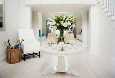A pedestal table is like a piece of functional art in an all-white foyer.