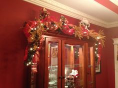 Christmas Chins Cabinet swag using mixed ribbons, multiple ornaments and gold filler with Santa Claus figurines on top. (Hamptons--November 2015). Designer Sidney Nicholson. Southern Traditions--Booneville, MS 662-728-1876.