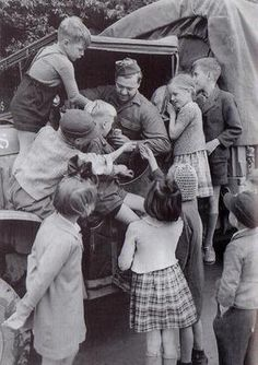 """Chocolate and chewing gum - German children """"besieging"""" a G.I., Germany 1945."""