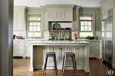 Pottery Barn barstools are pulled up to the kitchen island; the refrigerator is by Sub-Zero, the range is by Wolf, the sink fittings are by Perrin & Rowe, and the cabinetry paint is by Farrow & Ball.