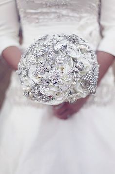 A white bouquet is accented with pearl and crystal embellishments. Click to check out other fabulous bridal bouquets.