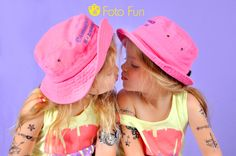 beautiful twin girls with pink hats kissing