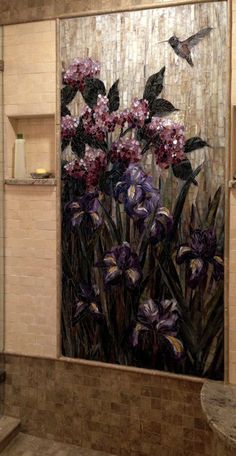 This is a shower insert glass mosaic mural with hummingbird, iris and hydrangea in Seattle, WA area. by Showcase Mosaics