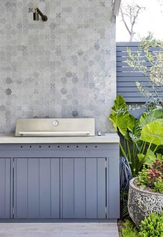 A Balmain terrace garden's dramatic transformation Patterned Morroccan style tiles line the wall behind the inbuilt barbecue in the outdoor kitchen space. The stainless steel appliance sits on a white benchtop and charcoal-blue cabinetry. Outdoor Tiles, Outdoor Spaces, Outdoor Living, Outdoor Bbq Kitchen, Outdoor Kitchen Design, Outdoor Kitchens, Outdoor Barbeque, Kitchen Grill, Kitchen Tiles