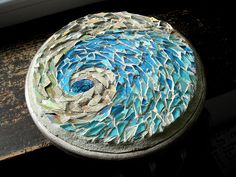 A challenge to use beach colors, with glass tile, silver and copper smalti, stained glass, mother of pearl, and abalone shell center, on wood, 8""