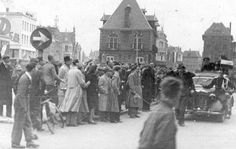 Groepen burgers en een bijzondere auto met autoriteiten op de Nieuwestad te Leeuwarden, tijdens de Bevrijding.